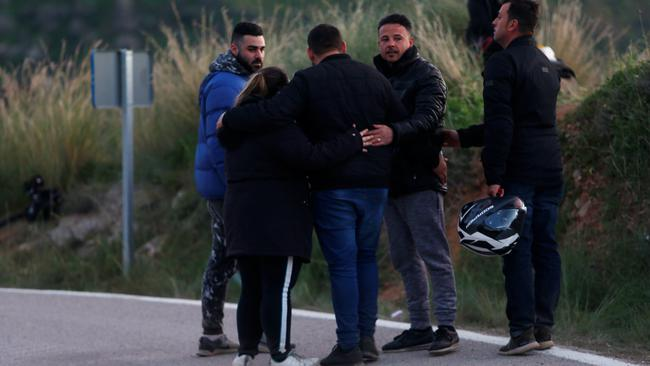 People comfort each other on a road after leaving the area where Julen, a Spanish two-year-old boy who fell into a deep well four days ago in Totalan