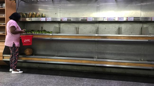 A woman selects lemons from partially empty shelves at the fruits and vegetables area in a supermarket in Caracas