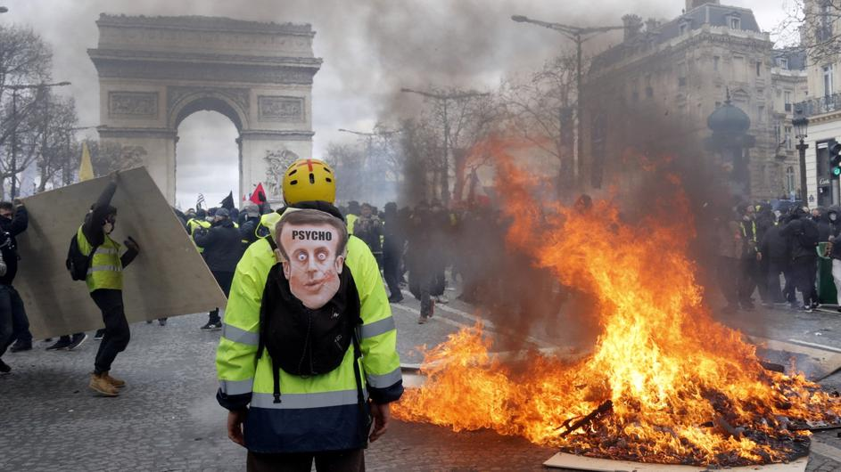 "A demonstrator stands near a burning barricade during a demonstration by ""yellow vests"" in Paris"