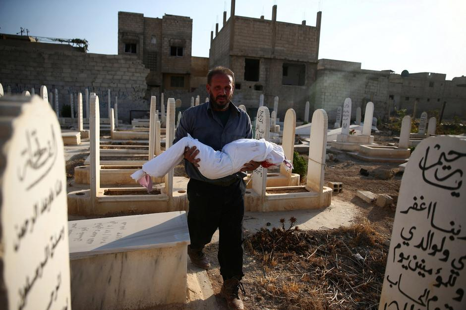 A man carries the body of dead child wrapped with cloth prior to burial in a graveyard after shelling in the rebel held besieged town of Douma, eastern Ghouta in Damascus | Autor: BASSAM KHABIEH