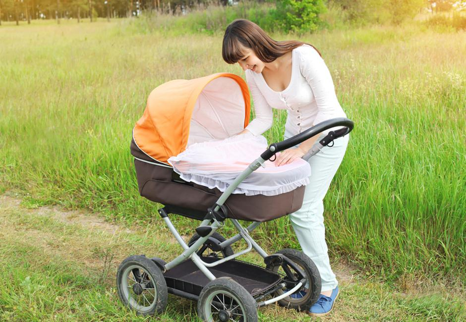 Happy young smiling mother walking with baby stroller outdoors o | Autor: Dreamstime