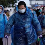 People wear face masks and plastic raincoats as a protection from coronavirus in Shanghai