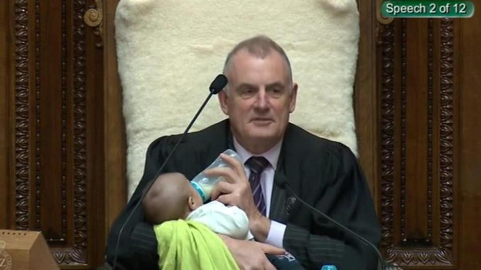 Screenshot from a Parliament broadcast of New Zealand Speaker Trevor Mallard feeding a Member of Parliament's baby during a parliamentary session in Wellington