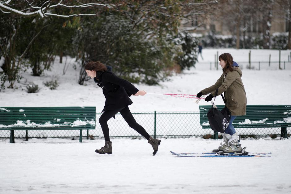 A young woman pulls another who uses skis in the Parc Monceau as winter weather bringing snow and freezing temperatures continues in Paris | Autor: BENOIT TESSIER
