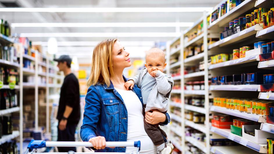Young mother with her little baby boy at the supermarket.