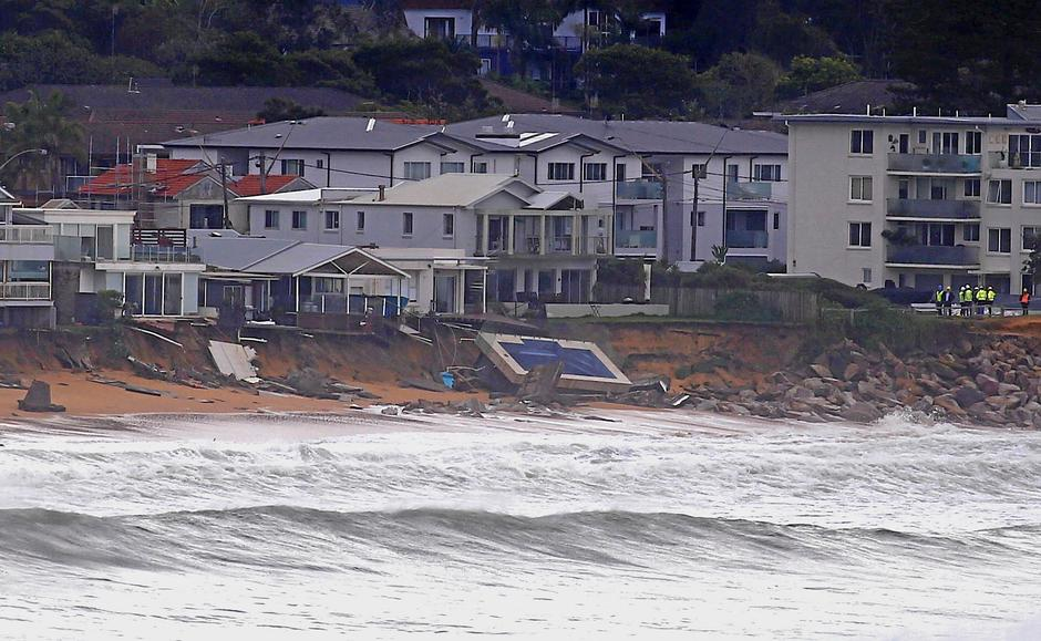 Officials stand near a swimming pool and houses that suffered damage after severe weather that brought strong winds and heavy rain to the east coast of Australia at Collaroy beach in Sydney, Australia | Autor: DAVID GRAY