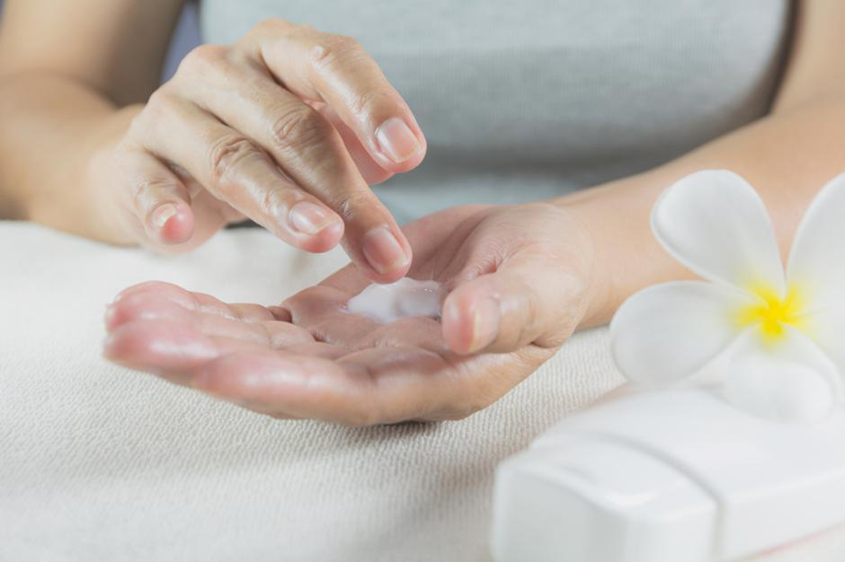 hand of woman apply lotion on skin of hand with lotion bottle on | Autor: Dreamstime