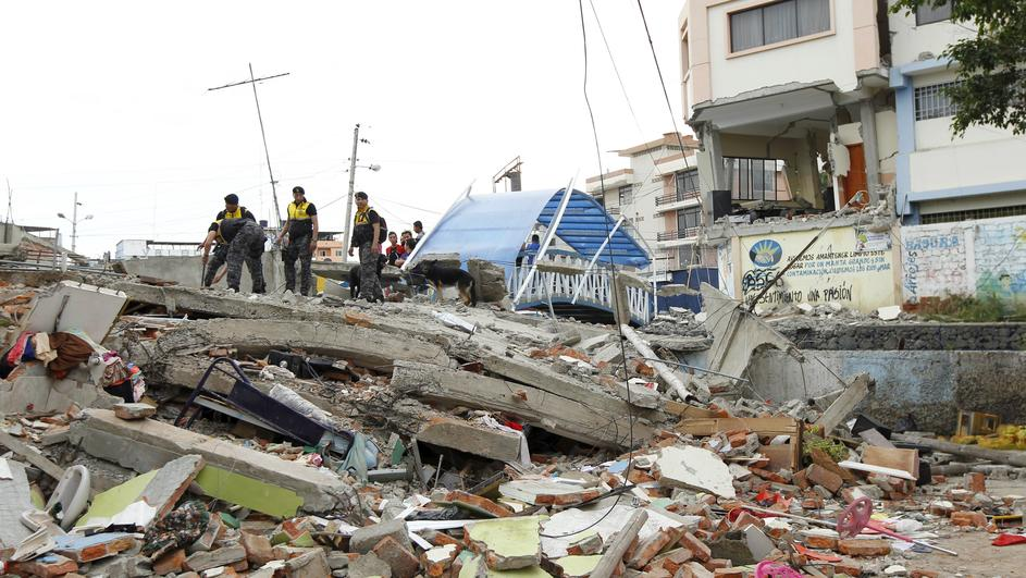 Police officers stand on debris after an earthquake struck off Ecuador's Pacific coast, at Tarqui neighborhood in Manta