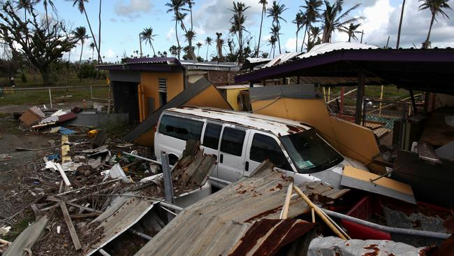 FILE PHOTO:  A car is partially buried under the remains of a building, after Hurricane Maria hit the island in September, in Humacao