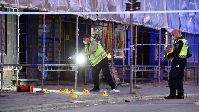 Police forensics investigate the scene after people were shot and injured outside an Internet cafe in central Malmo