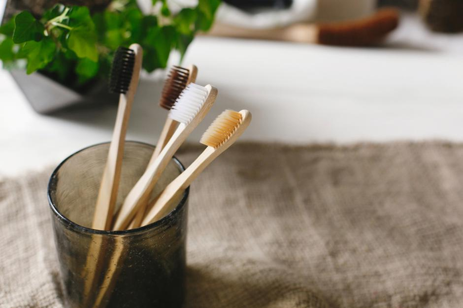 eco natural bamboo toothbrushes in glass on rustic background wi | Autor: Dreamstime