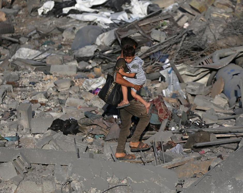 Palestinian boy carries his brother as he walks through the debris of a house destroyed in an Israeli air strike in the southern Gaza Strip | Autor: IBRAHEEM ABU MUSTAFA/REUTERS/PIXSELL/REUTERS/PIXSELL