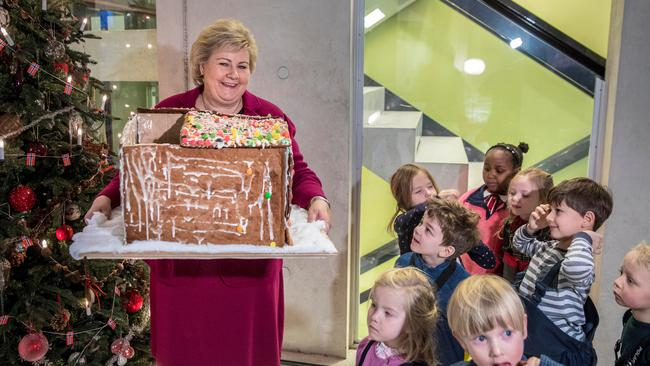Norway's Prime Minister Erna Solberg holds a ginger bread house given by children from a local kindergarten visiting her office in Oslo