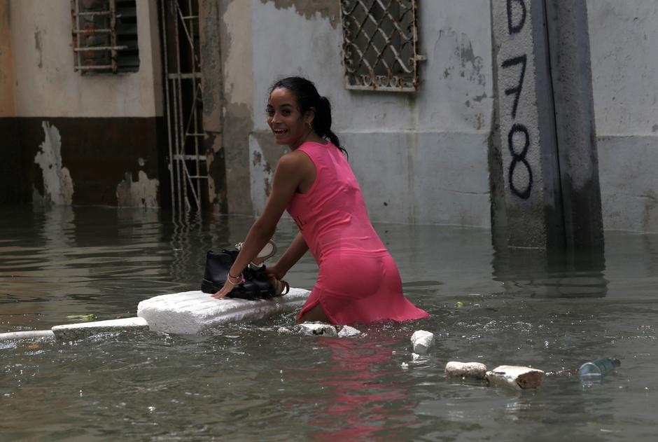 A woman keeps her shoes dry on a piece of foam board while wading through a flooded street, after the passing of Hurricane Irma, in Havana | Autor: STRINGER