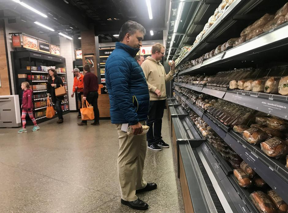 "Customers browse packaged wraps, sandwiches and salads at Amazon's new ""grab-and-go"" store in Seattle 