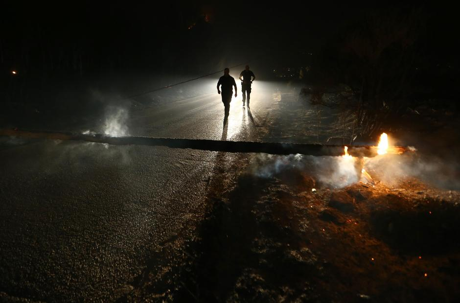 Local residents walk on the blocked road by timber,  burned by wildfire in the village of Mravince near Split | Autor: ANTONIO BRONIC