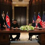 U.S. President Donald Trump and North Korea's leader Kim Jong Un sign documents, after their summit in Singapore