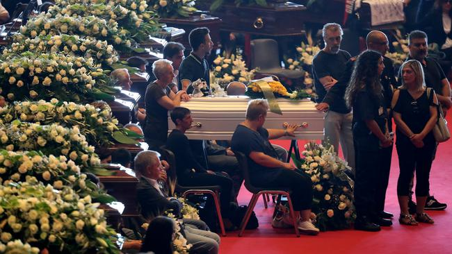 A relative touches the coffin during the state funeral of the victims of the Morandi Bridge collapse, at the Genoa Trade Fair and Exhibition Centre in Genoa