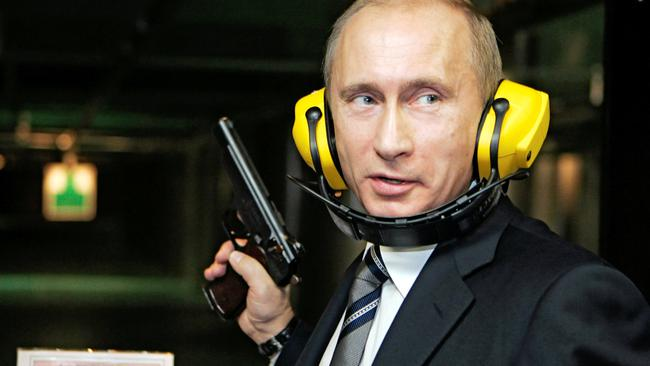 FILE PHOTO: Russian President Putin stands with a gun at a shooting gallery in Moscow