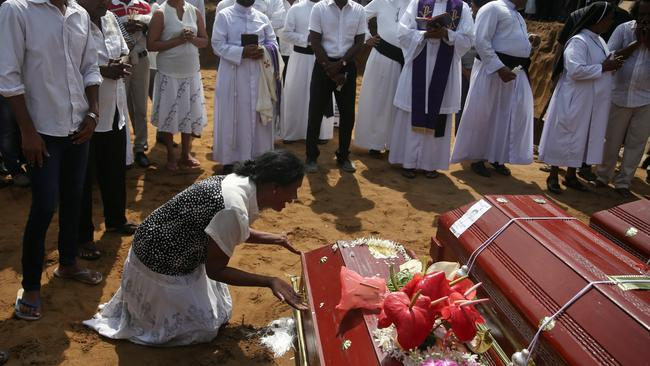 A woman reacts next to a coffin during a mass burial of victims at a cemetery near St. Sebastian Church in Negombo