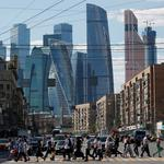"FILE PHOTO: Pedestrians cross the road as skyscrapers of the Moscow International Business Center, also known as ""Moskva-City"", are seen in the background in Moscow"