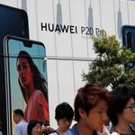 People walk past an advertisement for Huawei outside an electronic store in Tokyo