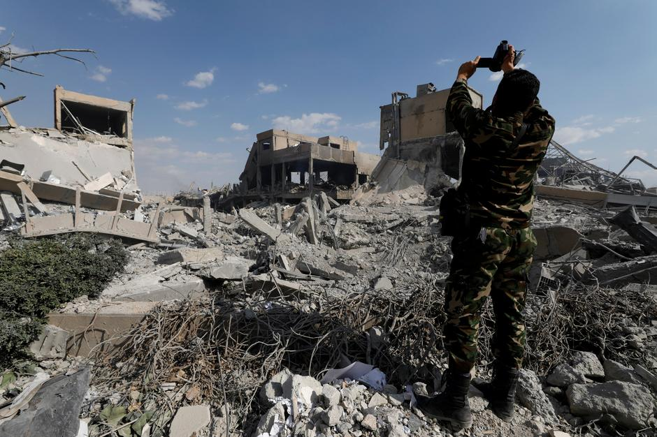 A Syrian military officer records a video inside the destroyed Scientific Research Centre in Damascus | Autor: OMAR SANADIKI