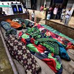 People look at the bodies of tea plantation workers, who died after consuming bootleg liquor, outside a government-run hospital in Golaghat