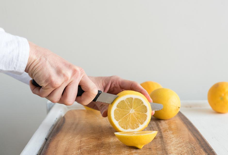 Middle aged woman's hands cutting lemons | Autor: Natalie Board