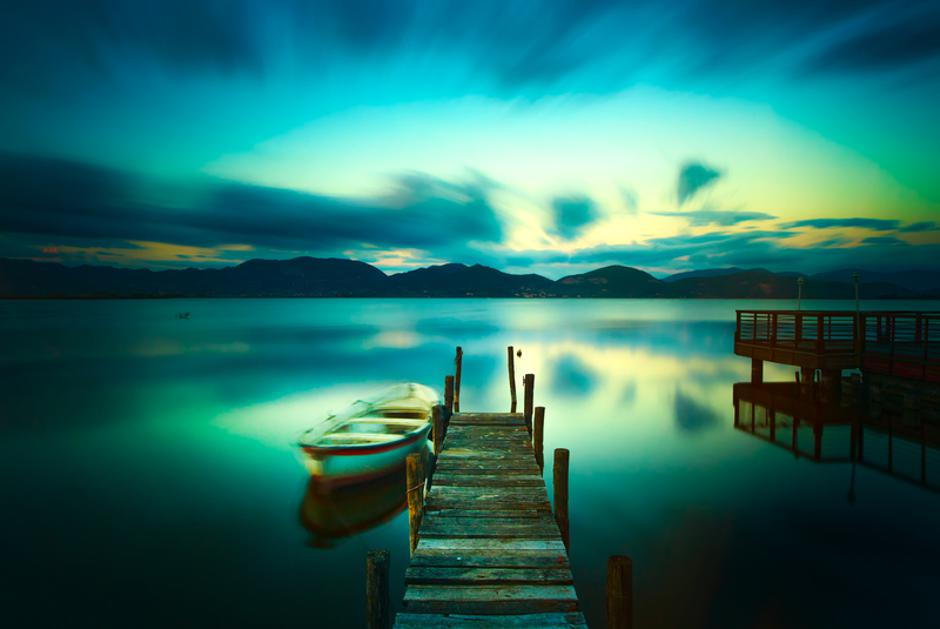 Wooden pier or jetty and a boat on a lake sunset. Versilia Tusca | Autor: Dreamstime