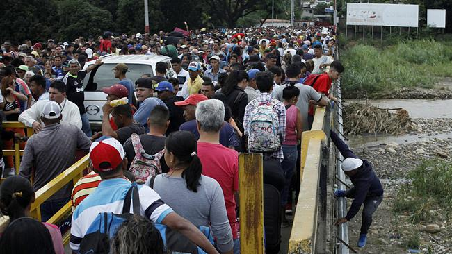 FILE PHOTO: A man gets off the bridge as people queue to try to cross the Venezuela-Colombia border through Simon Bolivar international bridge in San Antonio del Tachira