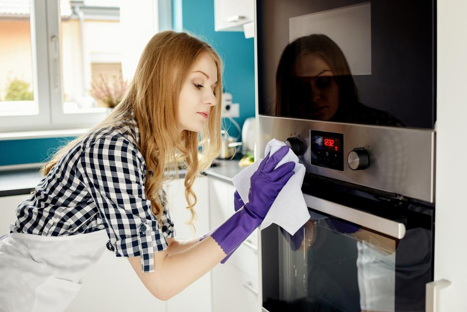 Beautiful blonde woman polishes stainless steel oven | Autor: DANIEL JEDZURA