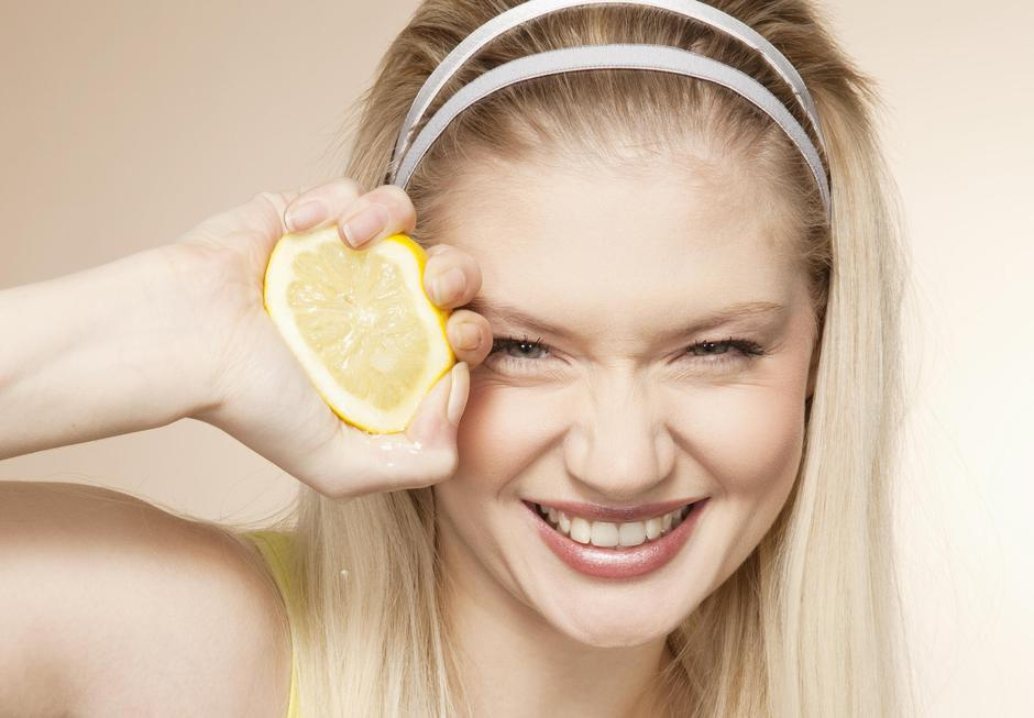 Young woman squeezing lemon, studio shot | Autor: altrendo images