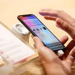 FILE PHOTO: A customer tests the features of the newly launched iPhone X at VIVA telecommunication store in Manama