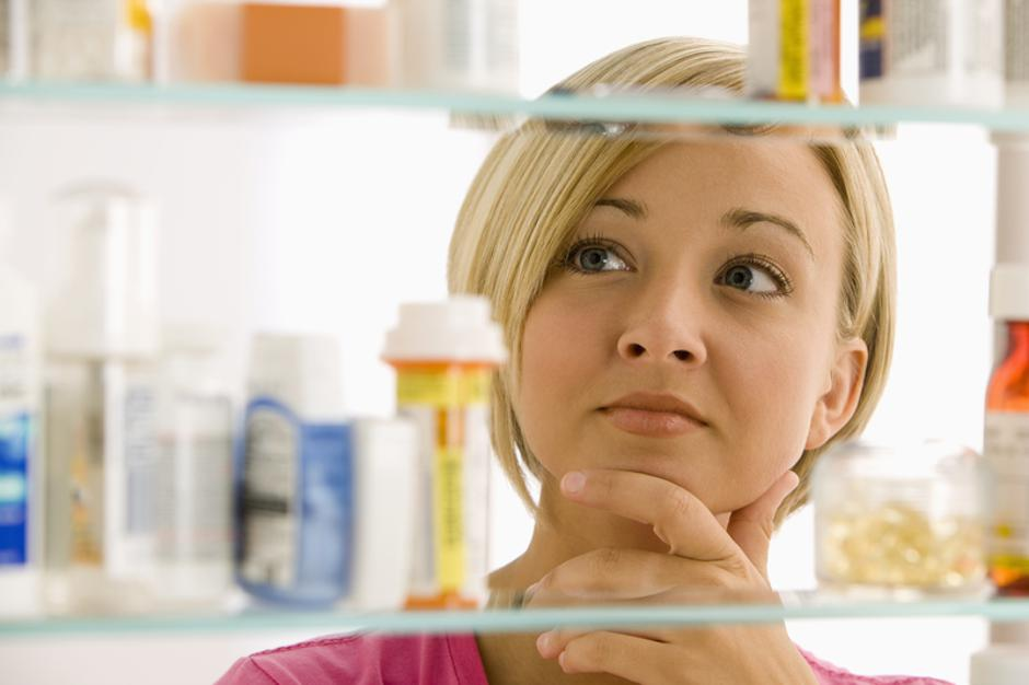 Woman Looking in Medicine Cabinet | Autor: Dreamstime