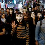 Anti-government protesters wear Guy Fawkes masks during a Halloween march in Lan Kwai Fong, Central district, Hong Kong