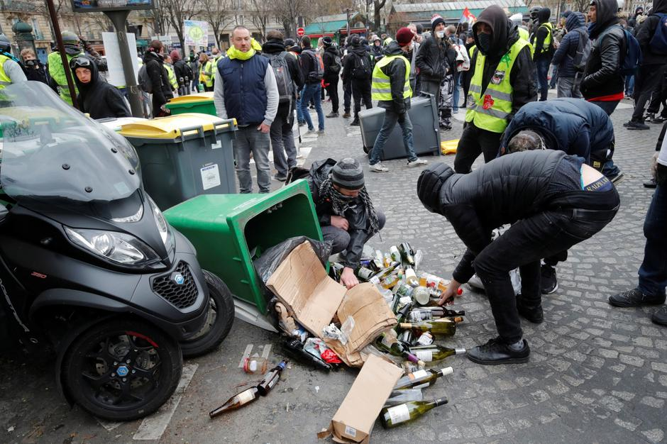 "Protesters pick up bottles during a demonstration by the ""yellow vests"" movement in Paris 