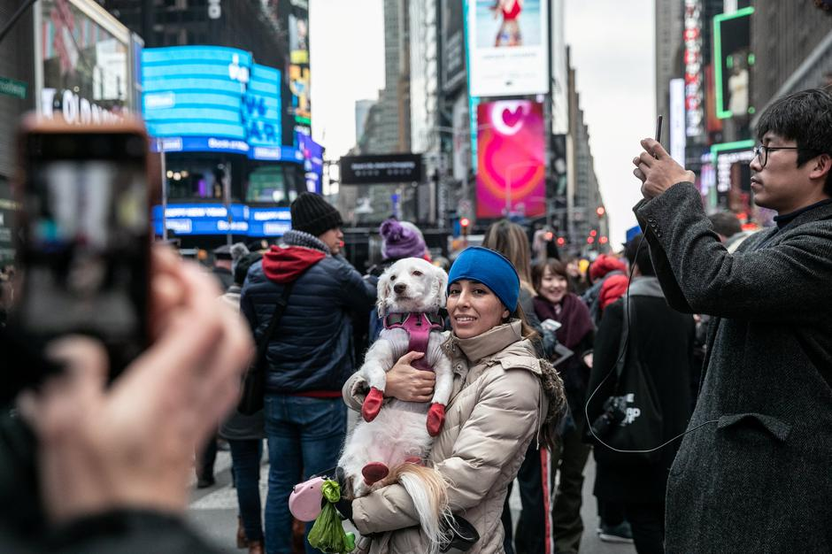 A reveler takes a picture with her dog the New Year's Eve in Times Square in the Manhattan | Autor: JEENAH MOON