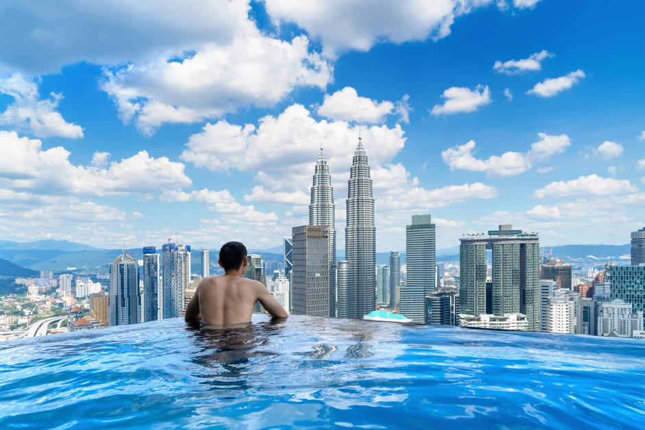 Back of tourist in a swimming pool on rooftop with Kuala Lumpur downtown view and blue sky. Malaysia travel trip in vacation and holidays concept in Asia. Skyscraper and high-rise buildings at noon. | Autor: tampatra