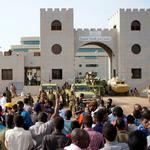 Sudanese demonstrators gather to protest against the army's announcement that President Omar al-Bashir would be replaced by a military-led transitional council, outside the Defence Ministry in Khartoum
