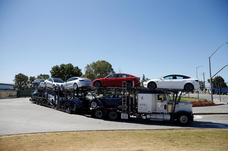 A car carrier trailer carries Tesla Model 3 electric sedans, is seen outside the Tesla factory in Fremont | Autor: STEPHEN LAM/REUTERS/PIXSELL/REUTERS/PIXSELL