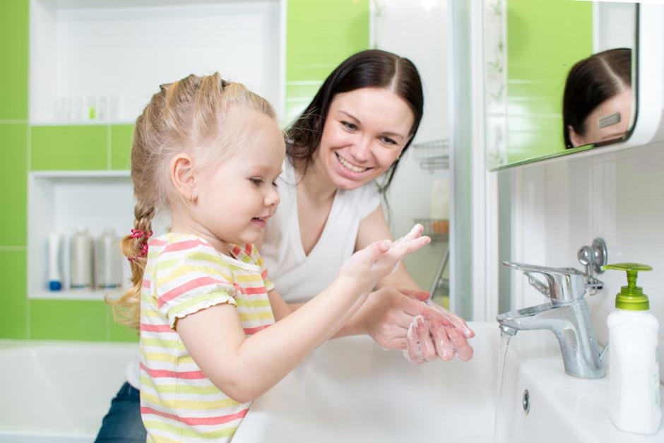 Happy mother and child washing hands with soap in bathroom | Autor: