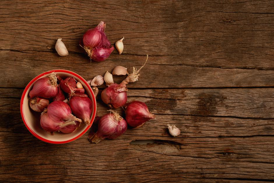 Onion and garlic in the cup on wooden floor. | Autor: