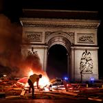 "A protester is seen next to a burning barricade during a ""Yellow vest"" protests against higher fuel prices, on the Champs-Elysees in Paris"