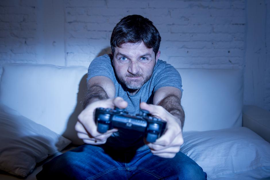 young excited man at home sitting on living room sofa playing video games using remote control joystick | Autor: Dreamstime