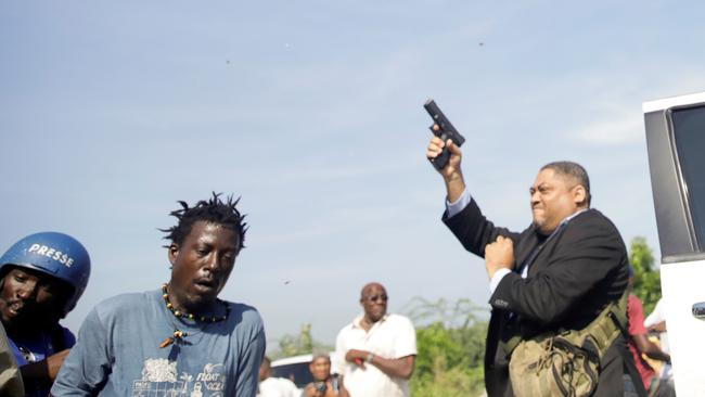 People run as Haiti's Senator Jean Marie Ralph Fethiere holds a gun in Port-au-Prince