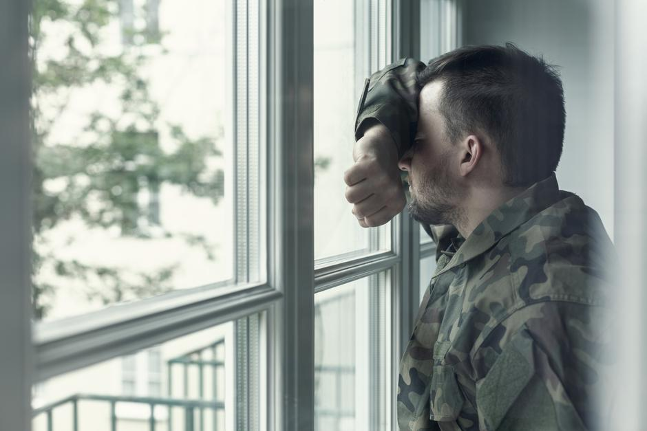 Depressed and sad soldier in green uniform with trauma after war standing near the window | Autor: Photographee.eu