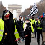 "A protester wearing a yellow vest and an Anonymous mask takes part in a demonstration by the ""yellow vests"" movement in Paris"