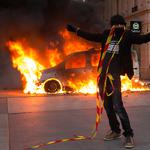 Demonstrators set car on fire in Paris