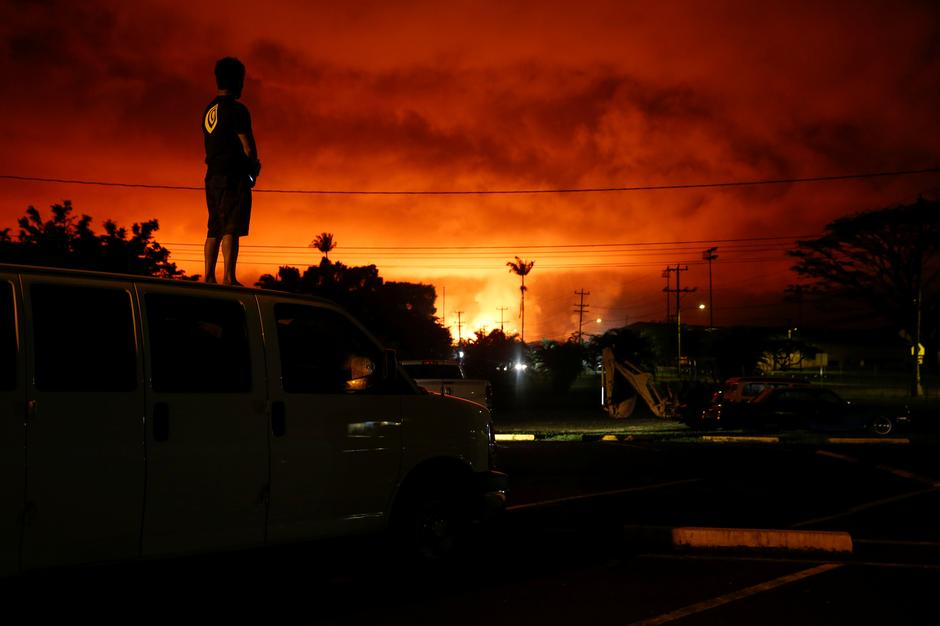 A man watches as lava lights up the sky above Pahoa | Autor: TERRAY SYLVESTER